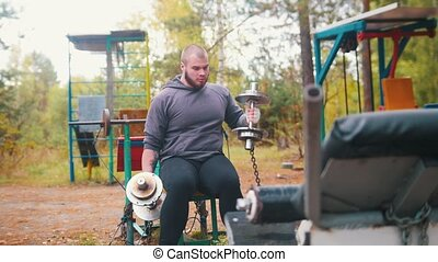 A man bodybuilder pulls up the dumbbells - training on the outdoors kids sports ground. Mid shot