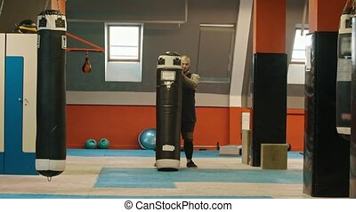 A man bodybuilder puts up the punching bag from the ground and putting it on his shoulder. Mid shot
