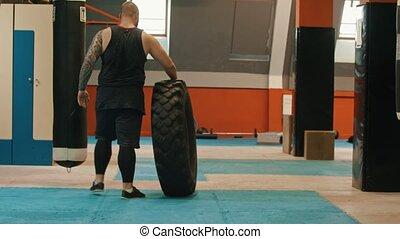 A man bodybuilder rolls a big tire in the gym. Mid shot