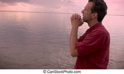 A man bowing his head in prayer in a still lake or ocean at sunrise