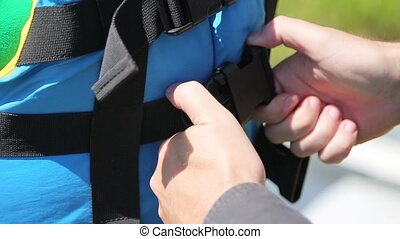 A man buttons blue lifejacket.