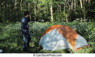 A man calling on the phone near the tent. Early morning in the forest