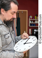 a man changes the time on a clock