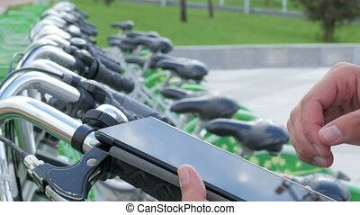 A man checks the messages on the Tablet PC on a bike parking lot. He's going to rent a bike