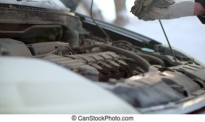 A man checks the oil level in the engine of his car. It is very cold