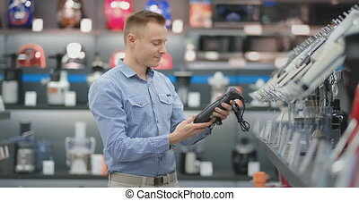 A man chooses a blender in the appliances store kitchen...
