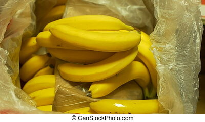 A man chooses bananas in the store, close-up, slow motion,...