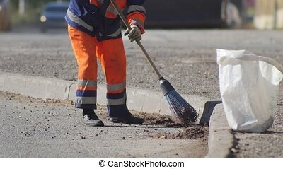 A man cleaning the asphalt with a broom. Mid shot
