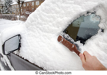 A man cleans the car from snow wih brush
