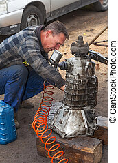 A man cleans the gearbox taken from