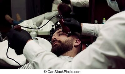 A man client visiting haidresser in barber shop, beard ...