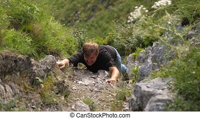 A man climbs on a rock attempt reaching the top of the cliff...