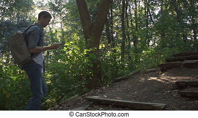 A man climbs up the hill, looks into the phone