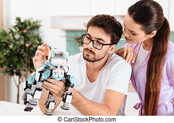 A man collects a robot in the kitchen. The woman...