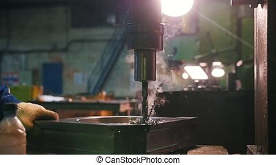 A man conducts drilling work in metal parts. There is smoke....