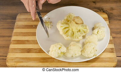 A man cooks cauliflower on cutting Board on the table from...
