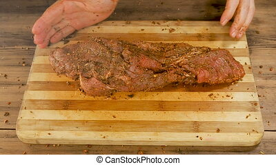 A man cooks meat on a cutting Board on the table from old wooden planks. Male hands sprinkle spices and crumple a piece of meat. Cooking pork, beef in the home kitchen. View of top