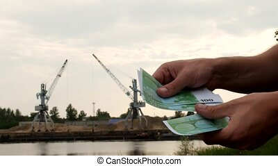 A man counts money euro against the background of cargo cranes that produce river sand in the port, receipts