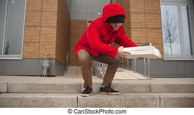 A man courier in red clothes walking out the building and takes a piece of pizza from the pizza box