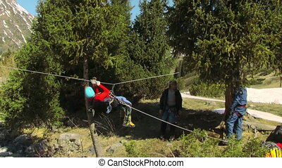 A Man Crossing The Mountain River By A Rope Crossing - a man...