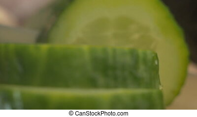 A man cuts a cucumber into slices on a black background in a...