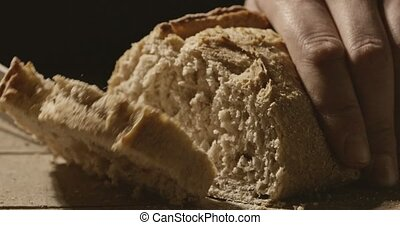 A man cuts a piece of white homemade bread on a wooden board...