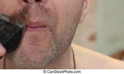 a man cuts his mustache trimmer