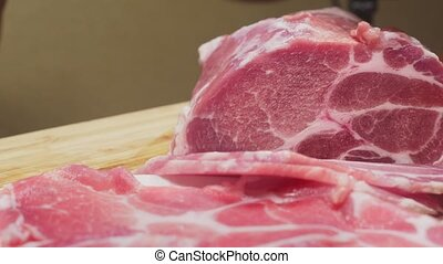 a man cuts raw meat with the knife in Slow Motion. 4k,...