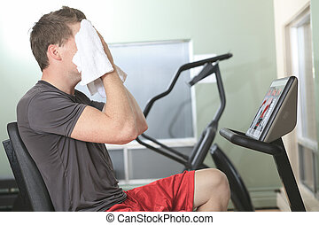 A man cycling on exercise bike in gym