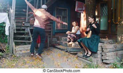 A man dancing russian folk dance - women sitting on the...