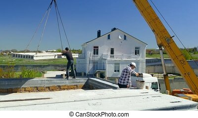 A man directs a concrete slab on the roof of the building