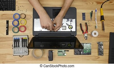 A man disassemble a laptop with a screwdriver. Wooden table top view.