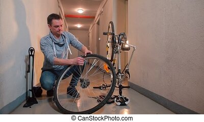 A man disassembles a bicycle wheel to seal a hole in the rubber.