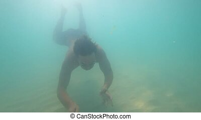a man dives into a crystal clear sea in a mask 4k