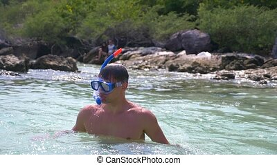 a man dives into a crystal clear sea in a mask and snorkel....