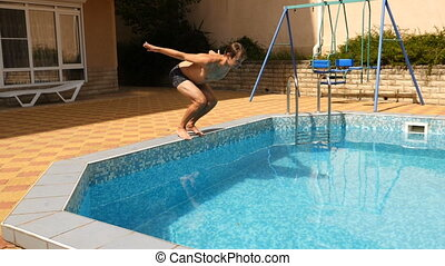 A man dives into the pool with blue water. Splashes fly in...