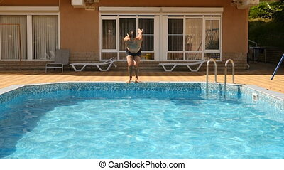 A man dives into the pool with blue water. Splashes fly in different directions. Slow motion