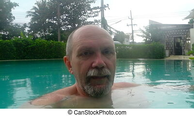 A man dives under the water in the pool and lets bubbles