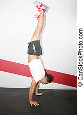 A man does a gymnastic handstand in the gym