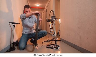 A man does a technical inspection of a bicycle wheel