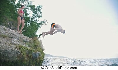A man does a trick in a jump in the river on a vacation in...
