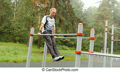 A man does push-ups on parallel bars