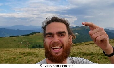 A man does selfie in the mountains. Joyous video, turn in a...