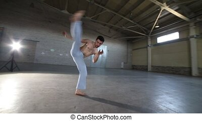 A man doing capoeira elements in the room with concrete...