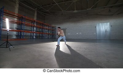 A man doing different capoeira elements in the room with...