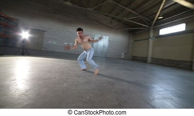 A man doing difficult capoeira elements in the room with concrete floor and brick walls - Mid shot
