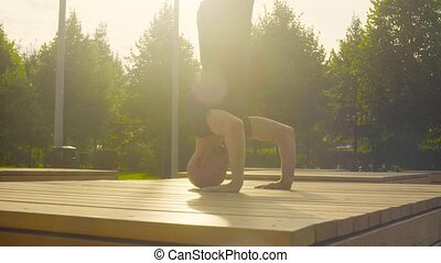 A man doing headstand in the park