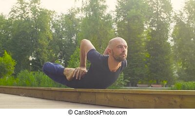 A man doing yoga exercises in the park