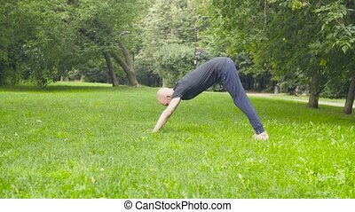 A man doing yoga exercises in the park. Surya namaskar -...