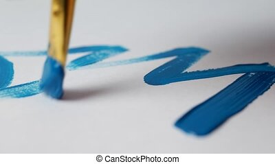 A man draws a blue paint on a white sheet of a Christmas tree, close-up, the new year 2109, Xmas